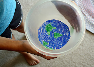 "Tessa created a mock Earth orbit with a drawing of the Earth taped into the bottom of a plastic bowl and a marble ""moon"" (the ""moon"" is the green blur on the right-hand side). She moved the bowl in a circular motion to experiment with centripetal and centrifugal force."