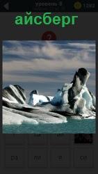 Около берегов океана плавают огромные айсберги под облачным небом, готовые развалиться на части