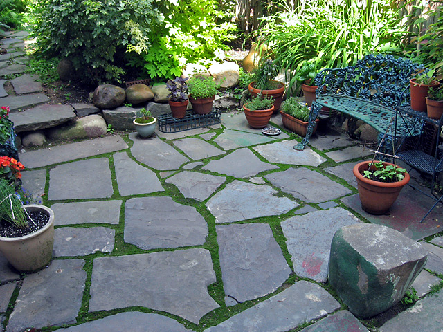 Reclaimed slate backyard patio Artist and Builder with moss and gardens