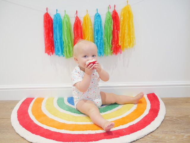 A rainbow rug sat on by a baby eating a cupcake
