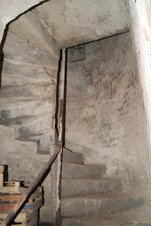 In einer Niesche windet sich eine Wendeltreppe nach oben