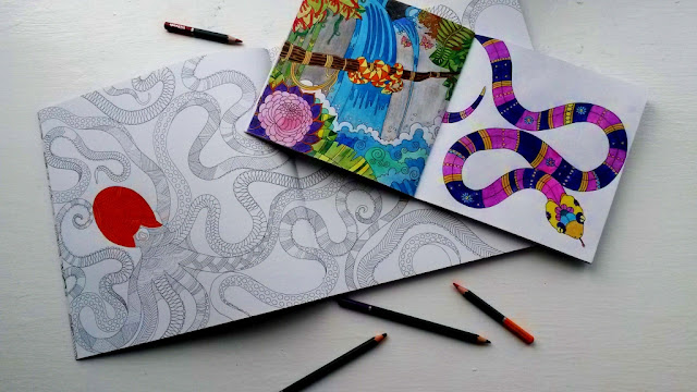 Coloured colouring book pages and pencils