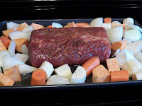 raw pork roast, carrots and potatoes in a baking pan