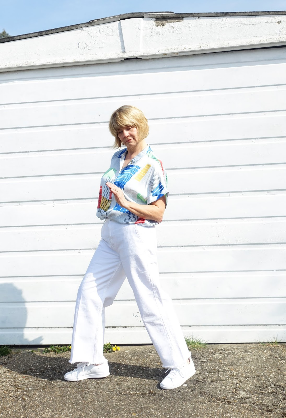 Throwing some shapes: woman in wide leg white jeans and geometric print short sleeved blouse
