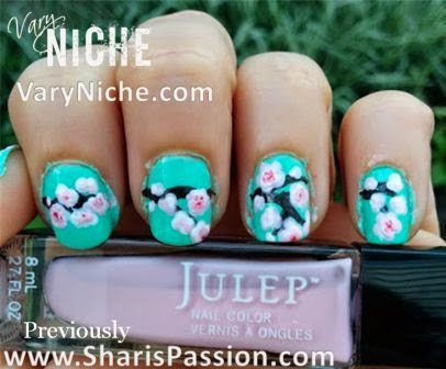 Fingernails with pale pink, white, & mauve flowers with tiny red centers dotted over a dark brown branch running across nails with a teal background.