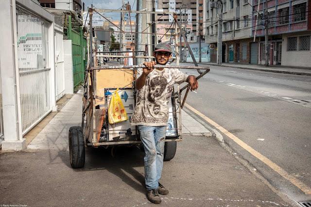 Trabalhados puxando o seu carrinho de coleta de materiais para reciclagem
