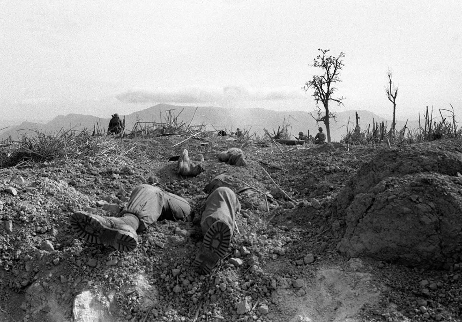 The bodies of U.S. Marines lie half buried on Hill 689, about two-and-a-half miles west of Khe Sanh, in April of 1968. Fellow Marines stand guard in the background after battling entrenched North Vietnamese troops for the hill.
