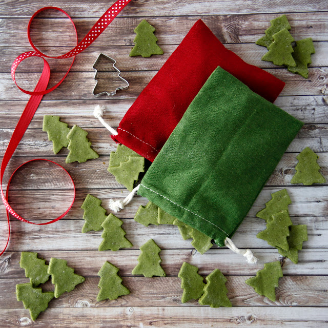 Homemade Christmas dog treats shaped like green trees on a table with red and green drawstring treat bags and ribbons