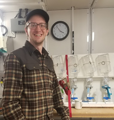 Photo of a smiling young man wearing a flannel jacket and hat, standing in front of a white filtration rack. The filtration rack consists of a row of 6 clear bottles secured upside-down over glass funnels filtering into white PVC pipes along the bottom of the shelf.