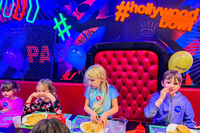Sitting down at a party table with neon lights children tuck into hot food