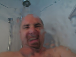 Man who lives in a van down by the river grimaces in cold shower. Vanholio.com