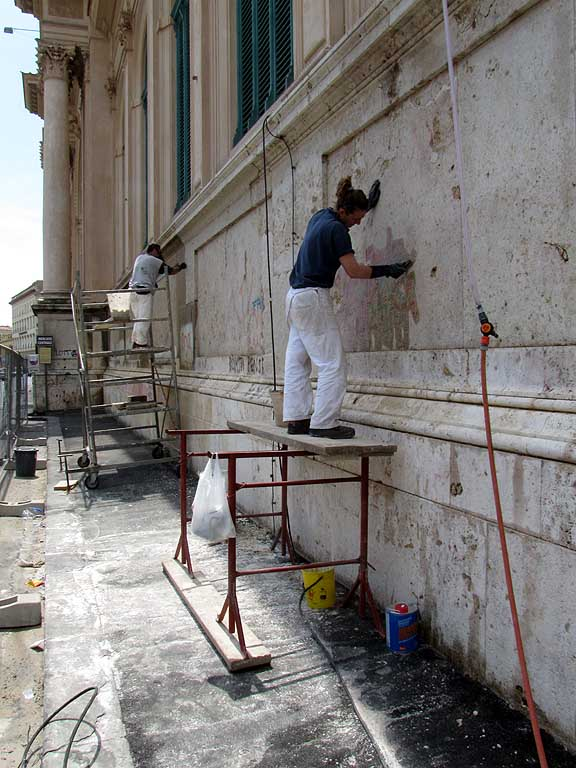 Erasing graffiti from the wall of the Central Market, Livorno