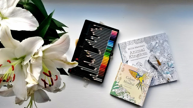Colouring books with coloured pencils and flowers