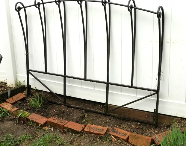 Repurposed bed frame trellis for the garden