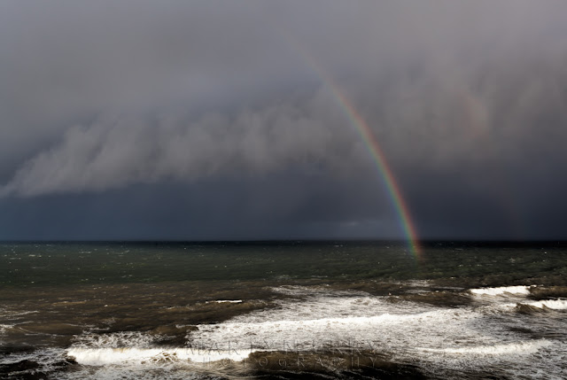 View from the Leas of a rainbow formation under a storm filled sky at Marsden