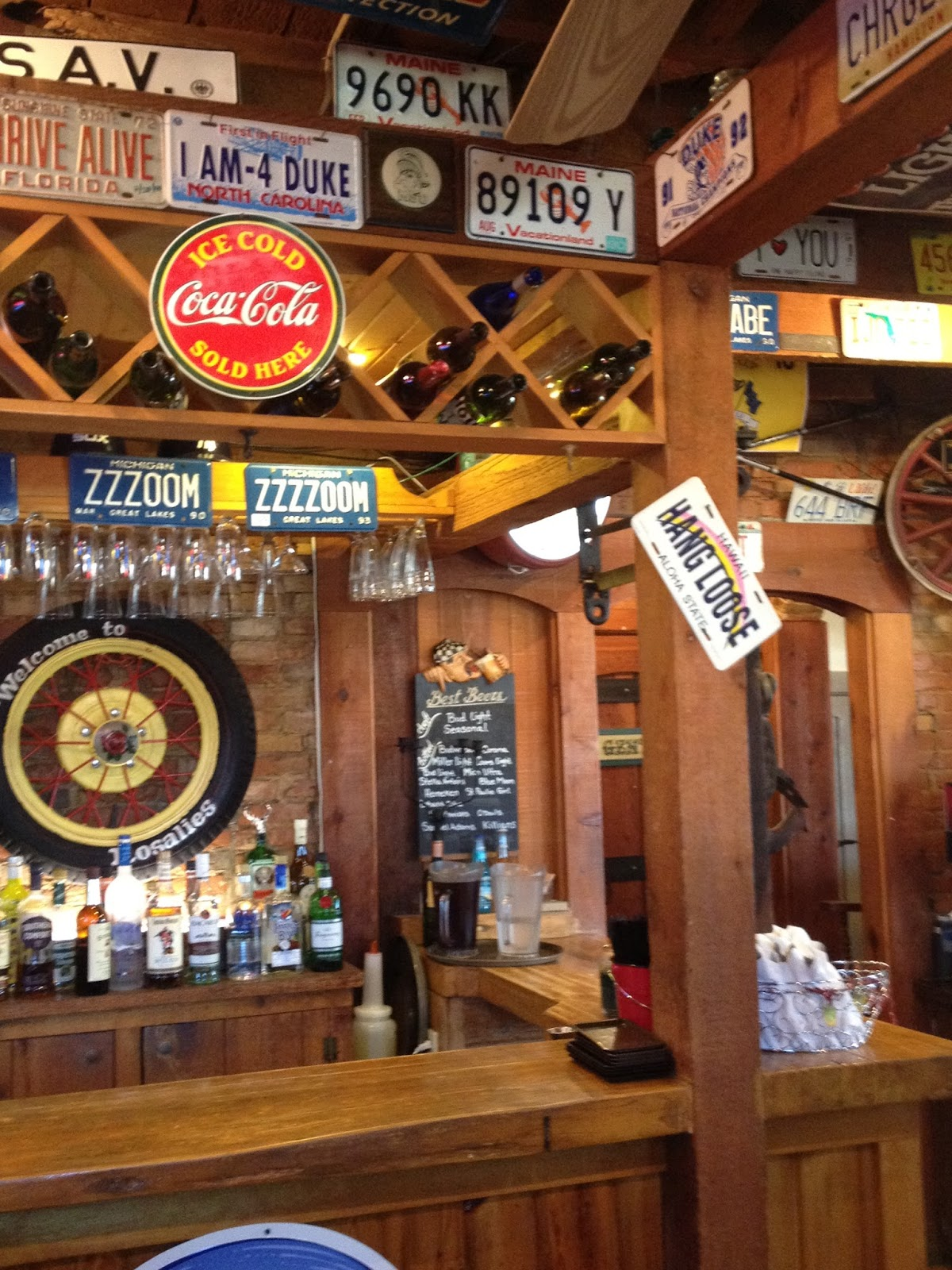 The Food Gets Served On A Pie Tin In Room Decorated With Automobile Memorabilia Vintage License Plates Dominate Walls And Ceiling Of Bar Area