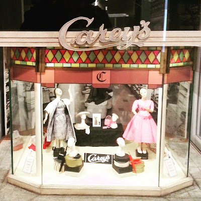 Model of a draper's front window with mannequins displaying frocks and hats. Several signs say 'Carey's'.