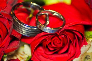 Cramer Imaging's professional photograph of wedding rings on a red rose bridal bouquet in Idaho Falls, Bonneville, Idaho