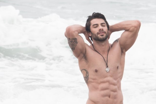 Foto de Renan Oliveira somente de sunga na praia, mostrando o corpo gostoso