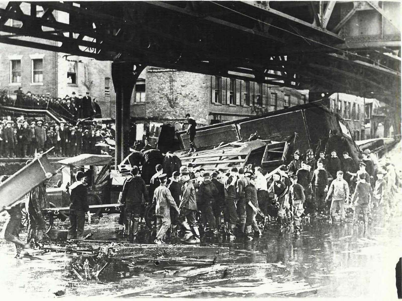 Rescuers tried desperately to save the occupants of the Clougherty house, which was torn from its foundation and smashed against the elevated train trestle by the molasses wave.