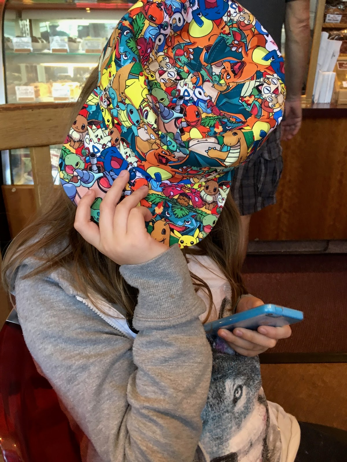 Child hiding behind a hat