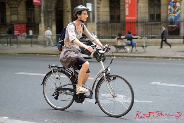 Woman in bike helmet, tee top and skirt over cycling pants, riding what is possibly a folding bike frame. Paris photos by Kent Johnson for Street Fashion Sydney.