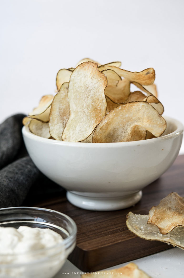 White bowl of golden brown salty potato chips