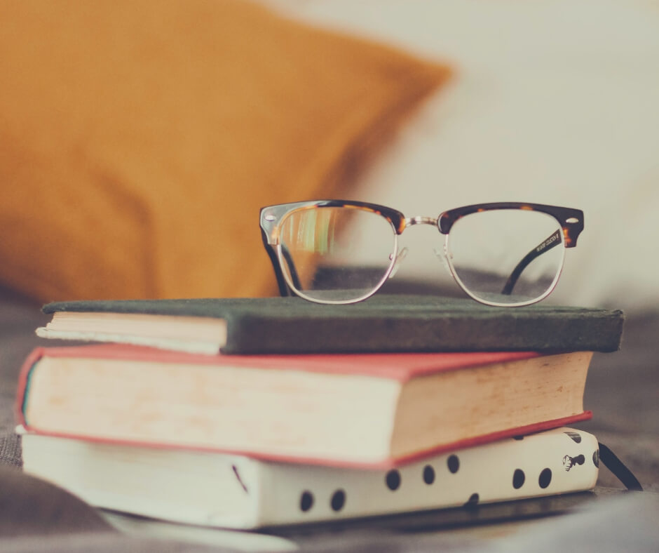 A pair of glasses sits on top of a pile of 3 books on a sofa.