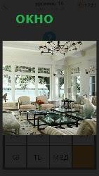 в помещении расположены большие окна, столы и стулья