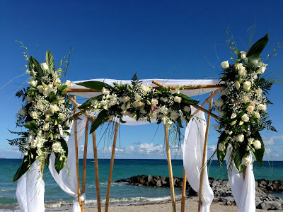 Beach wedding ceremony bamboo gazebo with flowers and white draping