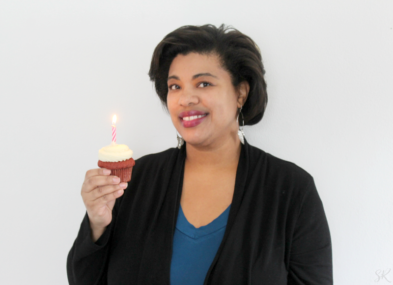 a woman holding a cupcake with candle