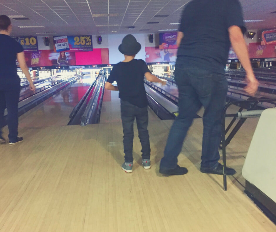 A young boy stands at the start of a bowling row in a bowling alley.