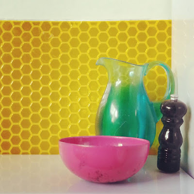 One-twelfth scale modern miniature still life with a water jug, bowl and pepper grinder against a wall of hexagonal tiles.
