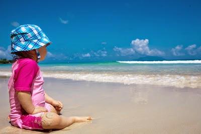Bébé assis sur la plage au bord de la mer à Mahé aux Seychelles