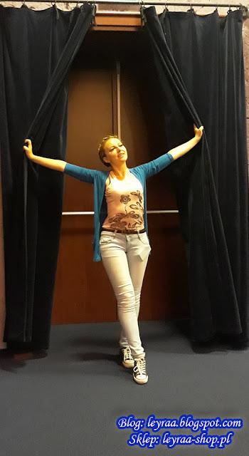 Granatowa narzutka, bokserka brzoskwiniowa z nadrukiem, jasno niebieskie jeansy, brązowy wąski pasek, czarne trampki, warkocz korona
