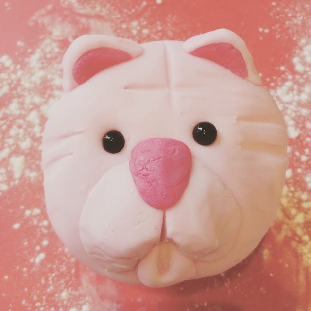 decorating a pink bear cupcake