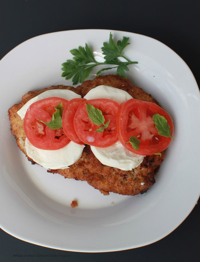 Fried steak cutlets with mozzarella, fresh basil and tomatoes on a white plate with sprigs of fresh parsley