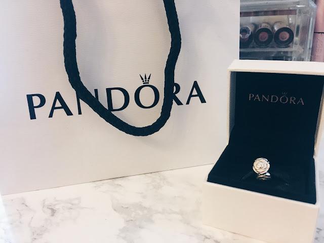Pandora gift bag next to a charm in a pandora box