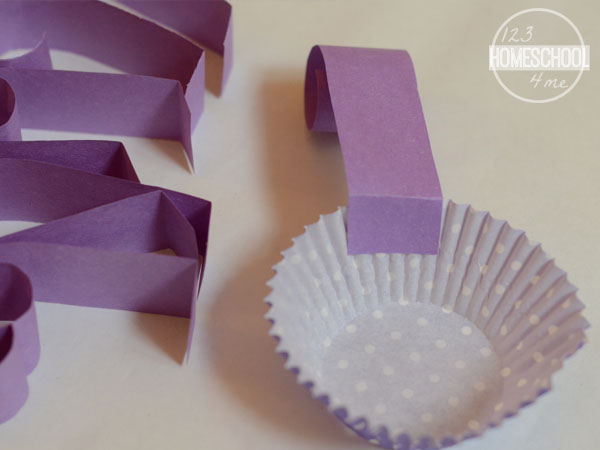 attach curled construction paper arm to cupcake liner