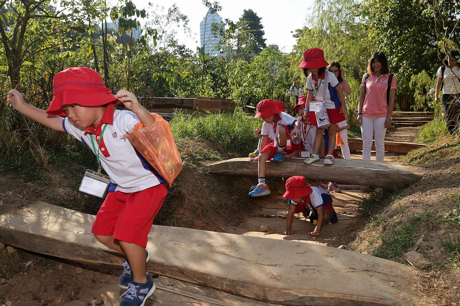 It's fun with dirt beneath their feet: Pre-schoolers from PCF Sparkletots enjoyed a fun day in the sun yesterday at Log Valley, one of the nine different play areas in the National Parks Board's (NParks) new Nature Playgarden at HortPark in Alexandra.