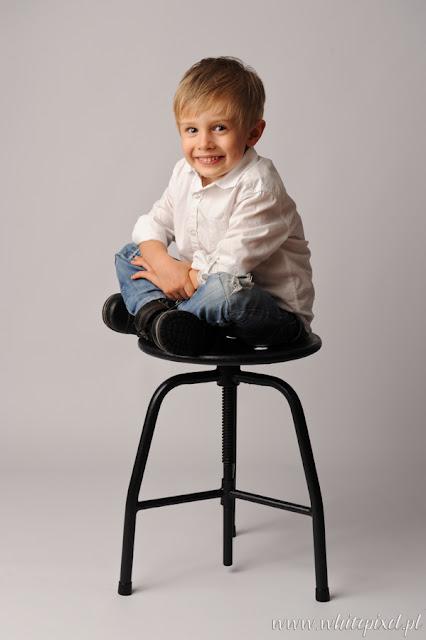 sesja chłopca na taborecie, fotografia uśmiechniętego wesołego małego chłopca, zdjęcie małego elegancika na tle