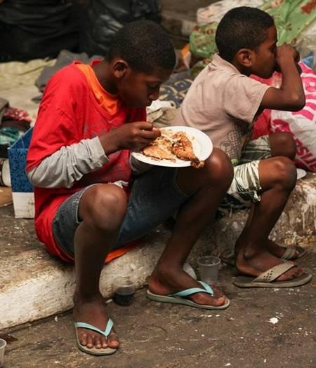 Crianças na calçada, comendo a  ceia de natal