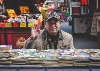 A bookseller at a table, making an ok sign.