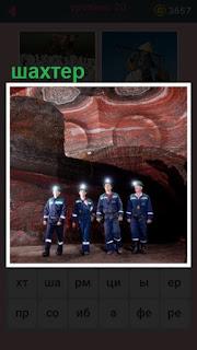 в пещере стоят несколько шахтеров в касках и специальных костюмах