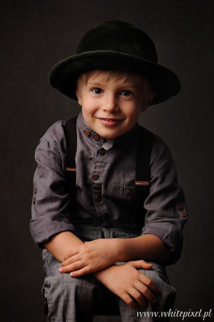 Fotografia uśmiechniętego czteroletniego chłopca w kapeluszu na ciemnym tle, retro stylowym, sesja w studio w Lublinie