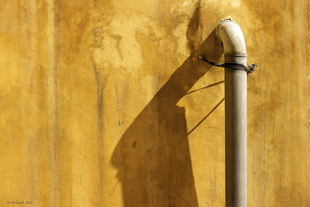 Minimalist Photo of Plastic Water Pipe and its Shadow on a Textured Brown Indian Wall.