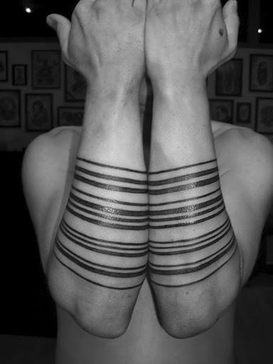 Uma série de antebraço bandas de tamanhos variados são retratados em tinta preta neste tatuagem conjunto.