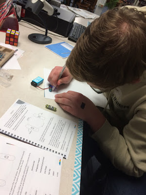 photo of boy working with battery