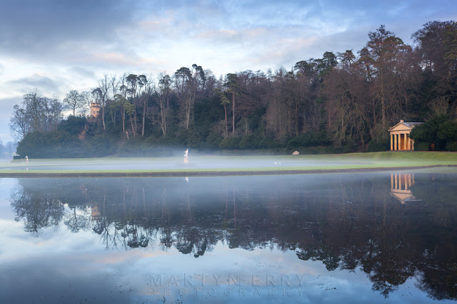 Temple and lake in the mist at the water garden at Fountains Abbey in Ripon North Yorkshire