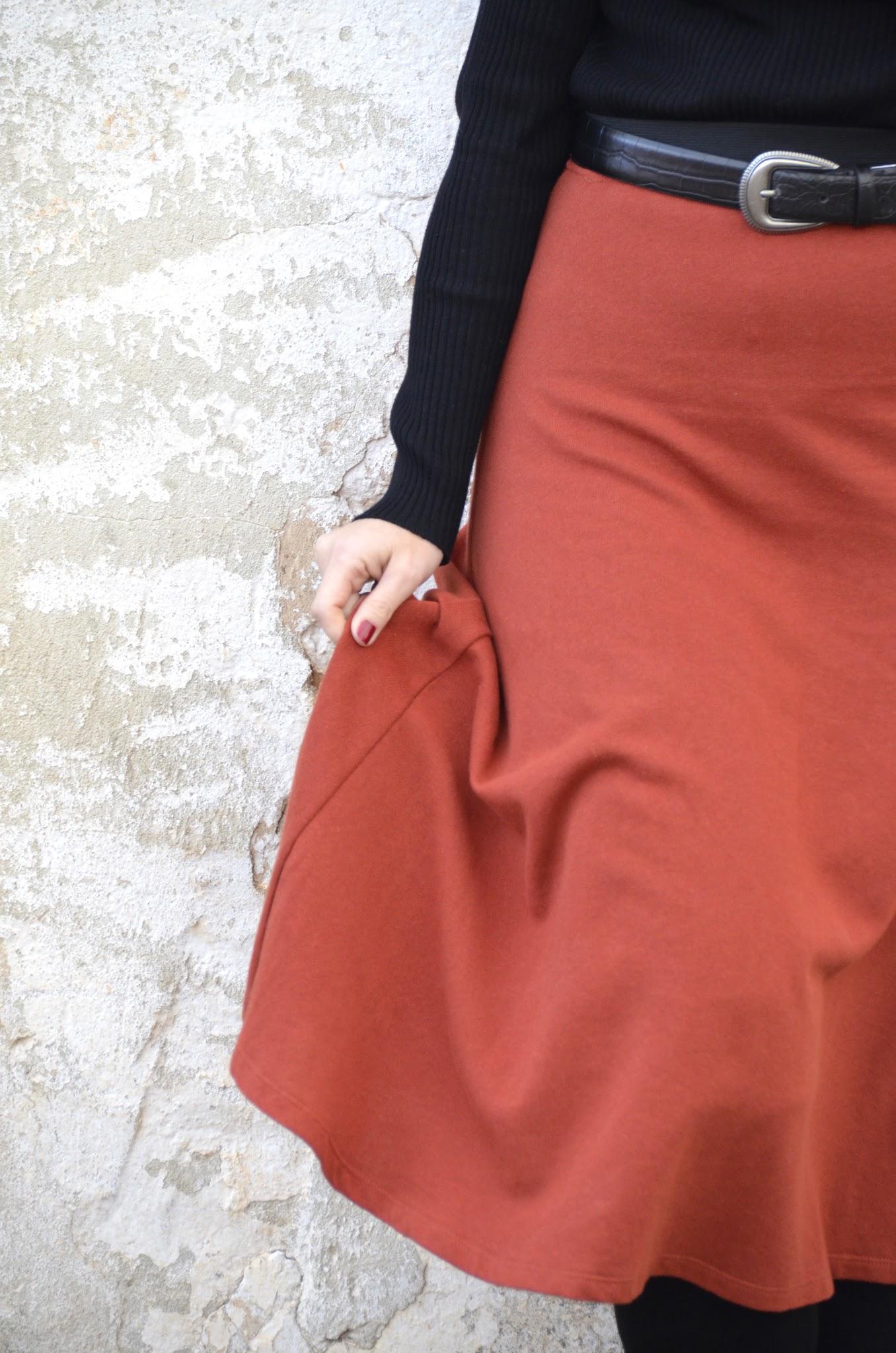 falda color teja y botas por encima de la rodilla